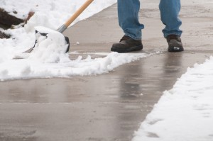 man uses a snow shovel to clear snow from a walk. Only the man's boots and the bottom of his jeans are visible.