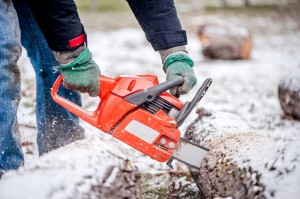 close-up of active male worker cutting firewood from snowy trees